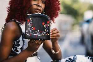 woman holding black leather handbag